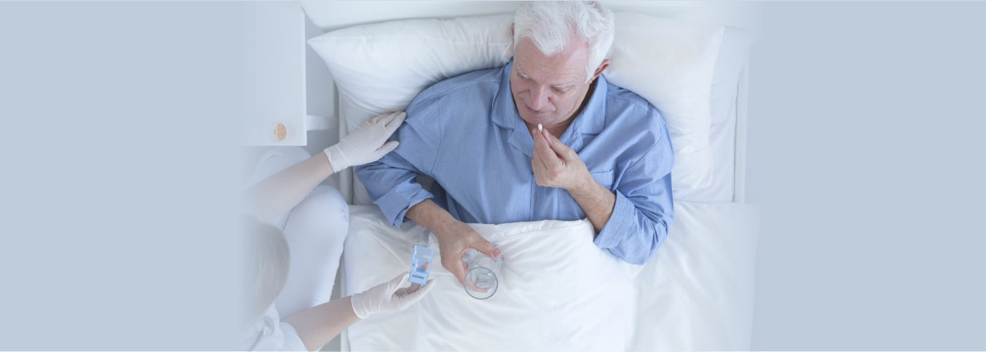 Patient lying in hospitl bed taking pill with glass of wate